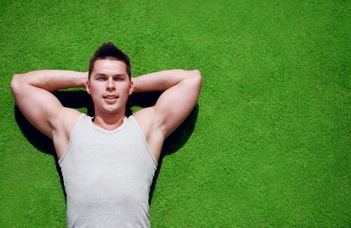 Fitness, sport - concept. Handsome man relaxing on the grass sum