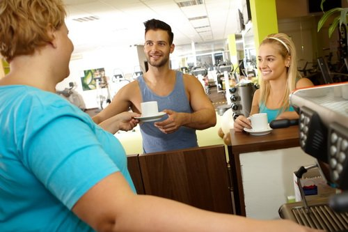 Overweight waitress serving coffee in gym