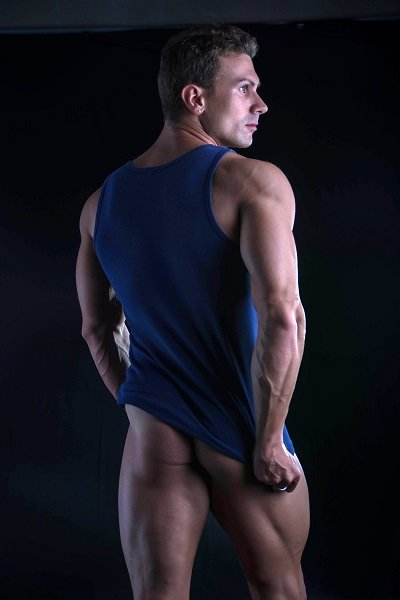 Back of young athletic man pulling down tanktop on ripped muscular torso