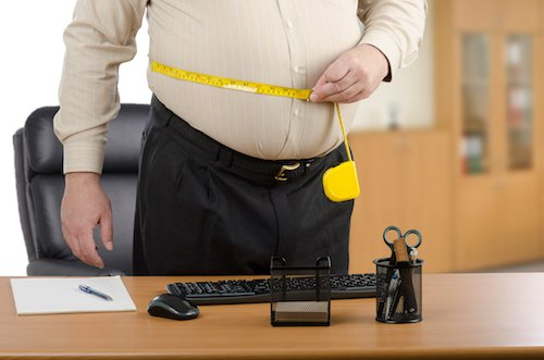 Man measures his waist by tape meter at the desk