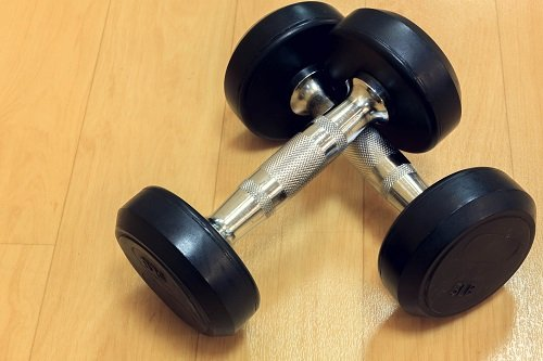 dumbbells on wood background.