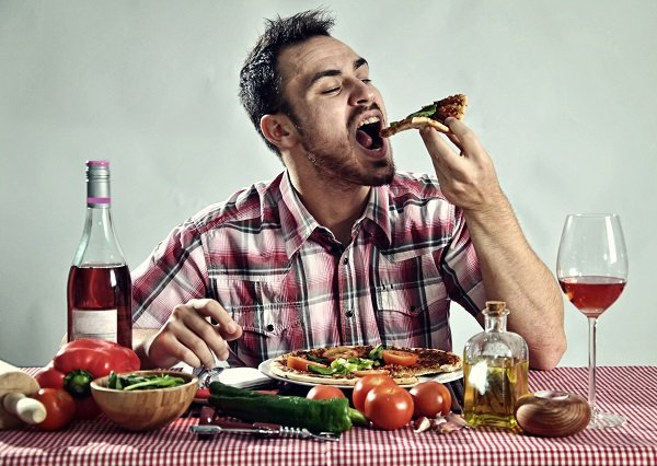 Crazy hungry man eating pizza