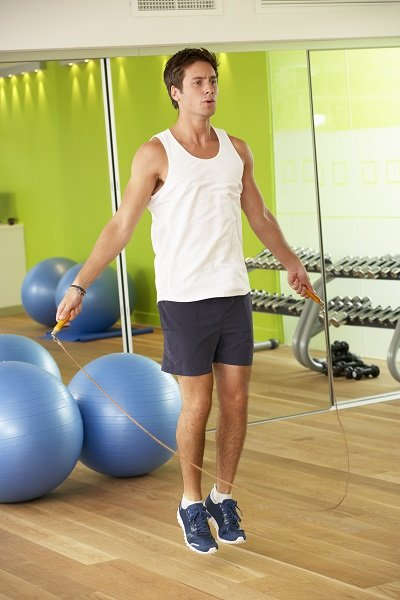 Man Exercising With Skipping Rope In Gym