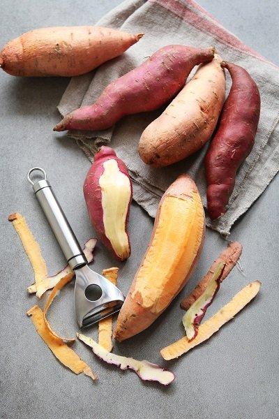 Two varieties of sweet potatoes on grey background