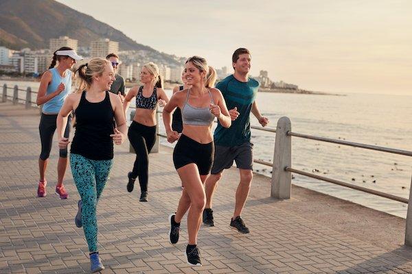 Group of athletes running along a seaside promenade