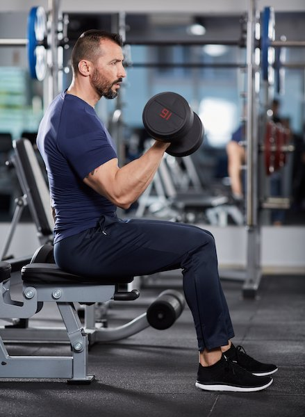 Man doing biceps curl seated